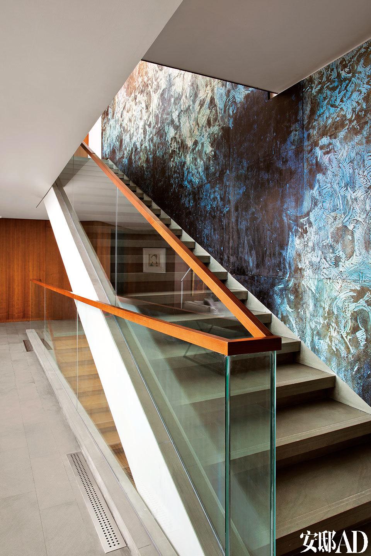 楼梯旁的壁画也是为这个家量身定制的,版画制作过程中的版,改变了原本的黑色调,铺满整面墙,贯通上下两层空间。二、三层之间有极具线条感的楼梯连接。楼梯旁的壁画出自艺术家杨宏伟之手,男主人说他最喜欢那一刀深一刀浅的刻度之间蕴含的内容。