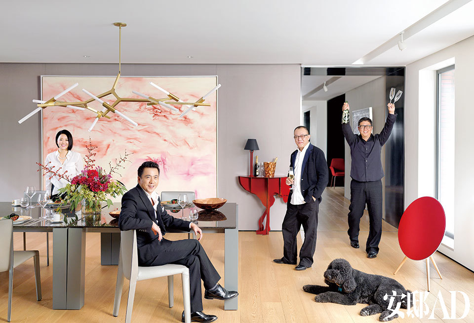"""王太与三位因重装工程而组成""""最佳拍档""""的男人一起在自家的西厨空间中享受""""庆功""""时刻,同时参加的还有爱犬""""拉菲""""。墙上大尺幅的艺术品来自曾梵志。青 色长餐桌来自Poliform,桌上的铜餐具来自Tom Dixon,红色鸵鸟边桌来自Ibride的Diva Lucia系列。人物从左至右依次为:王太、王中磊""""、家天地""""当代精品家具空间创始人、此家的家具装饰顾问任小勇、朱周空间设计(上海)创始人 兼室内设计创意总监Ray。"""