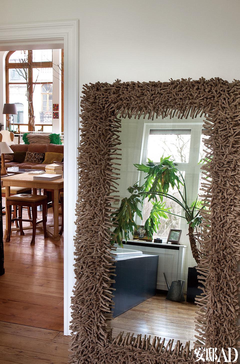 女主人选了许多Christian Astuguevieille设计的作品,搭配出不同味道,风格强烈的大块面镜子使得过道也成了一个看点。穿过门,客厅里同样出自他设计的桌子和椅子,又是另一种质朴感觉。