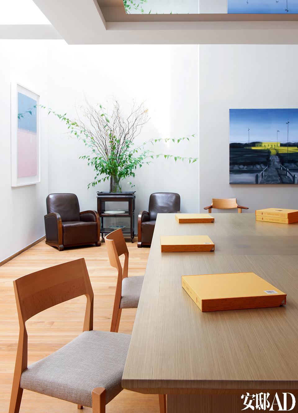 位于负一层的餐厅中,左侧墙上的淡粉、淡蓝色画作是艺术家谭平的版画作品,沙发和佐餐车是20世纪30年代上海AreDeco风格的古董家具,购自上海。正面墙上的油画来自艺术家张晓刚,主餐桌为定制品,餐椅是日本设计师的作品。