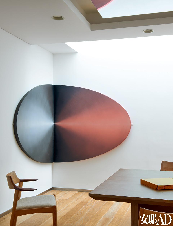 阳光从天花板边沿的挑空处倾泻下来,餐厅显得光线充足,家具和艺术品也因此被镀上一层柔和的光晕。餐厅的另一角,墙角上挂着艺术家陈文骥的油画作品,这幅作品曾经在同一平面上展示,如今摆成垂直的角度,别有一番风情。餐桌正上方的镜面装饰是渝儿的创意,餐椅是日本设计师的作品。