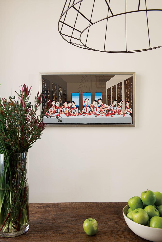 家中充斥着斯堪的纳维亚的简约、舒适氛围,却又处处暗藏东方元素,这与主人的经历相互吻合。书房墙面上,挂着一幅由曾梵志在2002年创作的《最后的晚餐》(13/89),购于上海。