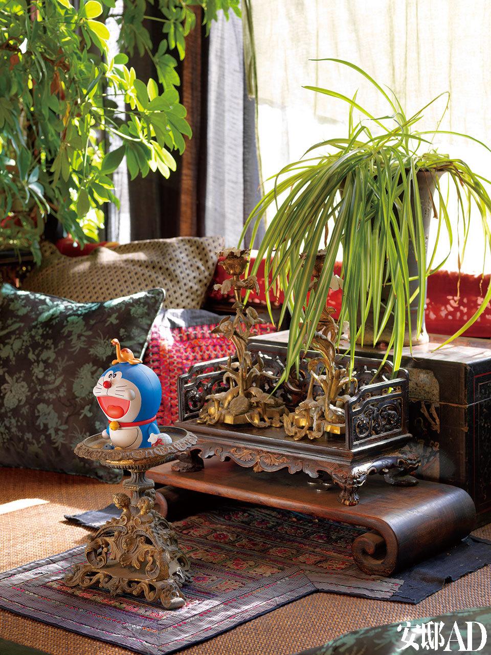 主人还喜欢把自己的心气藏在许多细节里,像客厅老架子上,似供台的小矮桌前却是头顶小乌龟的哆啦A梦,是不是很戏谑?