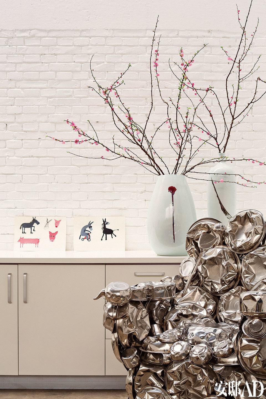 这面白墙如今也是家庭影院的背景墙,每当夜幕来临,一家人可以窝在对面夹层上的沙发中,温馨地看场电影。楼上工作室的一角,靠墙的两幅素描作品是A4团队的插画师Chen Bin为一个设计项目画的草图,两只花瓶来自Spin。