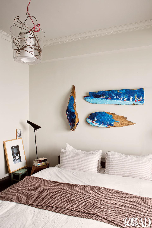 床头墙上的装饰,来自巴厘岛的旧渔船残片,床边的黑白照片是乌镇的摄影师作品。