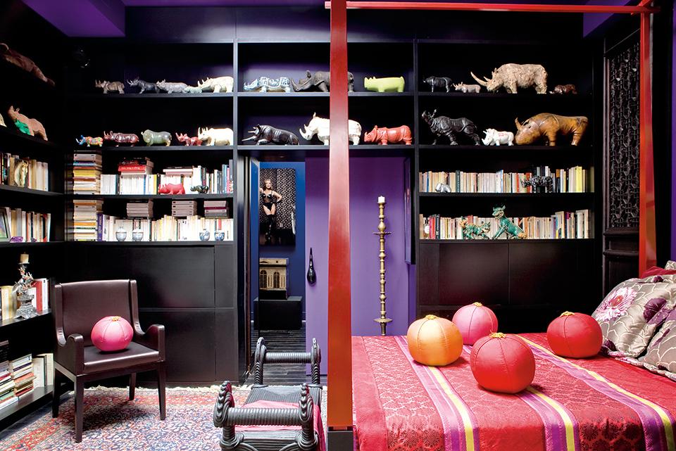 紫红色调的客房相当惊艳,这里还展示 着主人上百件大小不一的犀牛收藏。客房的红黑漆四帏柱床及扶手椅由Nicolas和Marc打造。真丝面料来自Designers Guild,丝绸靠垫出自一位中国设计师之手,主人于15年前购自巴黎。床前榻来自Christian Astuguevieille,门口的黄铜枝状大烛台购自摩洛哥,埃及地毯购自阿斯旺,多件犀牛藏品则来自世界各地。