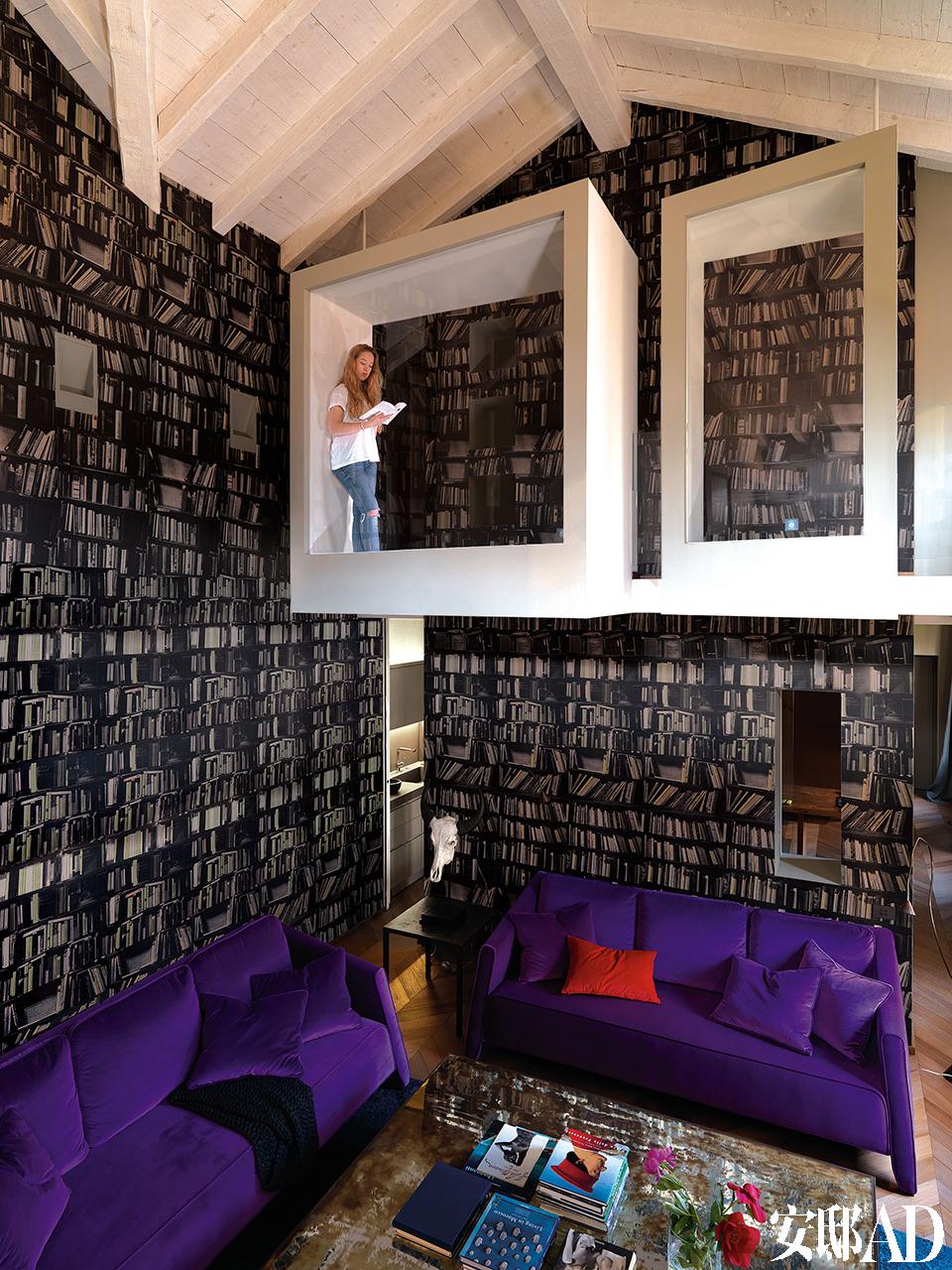 房屋主人的女儿Bianca正在很酷的冥想阅读室中看书,贴满通高墙壁的书架图案壁纸由Deborah Bowness设计。