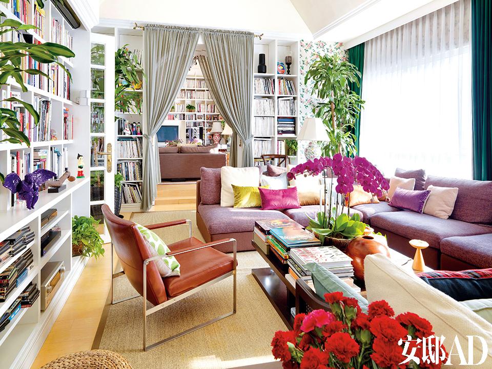 """家里有花朵壁纸、堆得都快倾倒的大书架、芬芳流动的鲜花植物和都快没地方放的各色小装饰……它们簇拥着他,才让他""""感到非常安心""""。主客厅与小休息厅通过一道法式落地门连接起来,碎花壁纸与色彩丰富的家具都被大色块的灰色窗帘和白色书架统一起来,既丰富活泼,又不显繁杂。"""