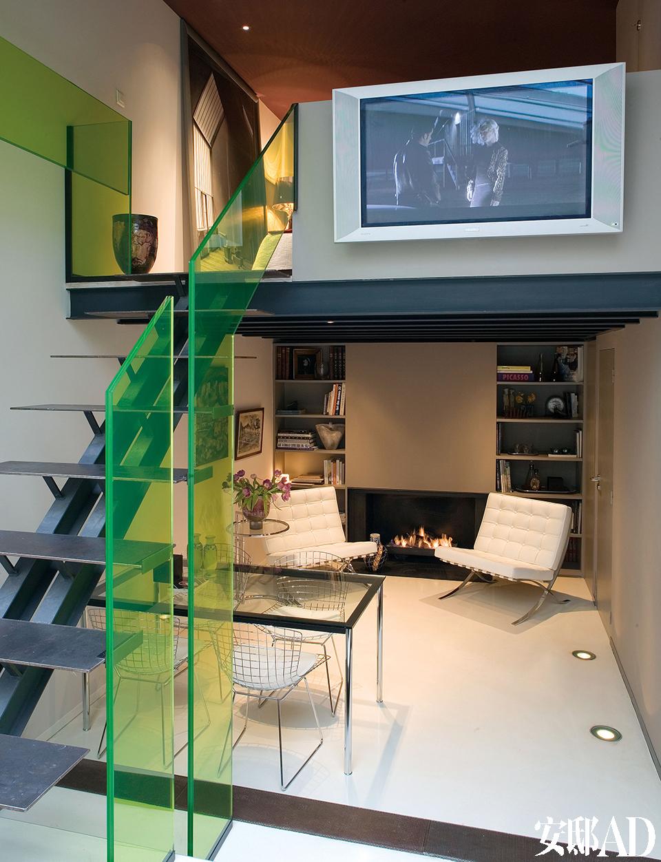 金属楼梯的每一级台阶都由钢条铺设,绿色玻璃扶手成为整个家的点睛之笔。两把白色巴塞罗那扶手椅与壁炉搭配成一个温暖的阅读区。从楼梯拾级而上,就是夹层卧室。夹层上的镀锌的陶罐来自Domani。