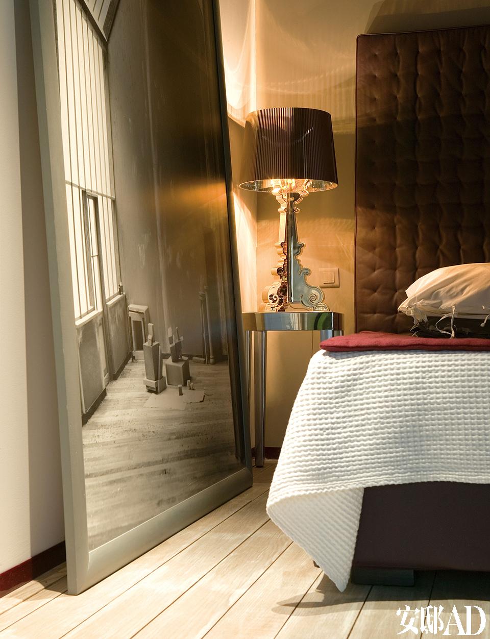 巨幅摄影作品揭示了这个家作为陶艺工作室的前身, 灰色调子中透出一丝属于往日的宁静。卧室铺装了淡雅的铅白色实木复合地板。真皮折叠床来自Orrizonti,金色的Bourgie台灯来自Kartell。巨幅摄影作品由Philippe Decobert创作。