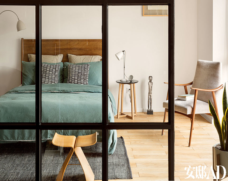 """一间卧室套间中,区隔出卧房与浴室的是一面巨大的法式黑框落地推拉门。木床和床上用品来自伦敦的West Elm,左侧的落地灯是Graham & Green品牌,右侧的床边桌来自Amara,小台灯购自巴塞罗那一家名为""""Punto Luz""""的灯具店。床下的地毯来自Vincon,这是巴塞罗那一家具备引领性地位的设计店,已经开了100年,很可惜最近关张了。窗边的单人扶手椅是一件中古家具,源自20世纪中期,重新包裹了天鹅绒面料,购自巴塞罗那的概念店Jaime Beriestian。"""