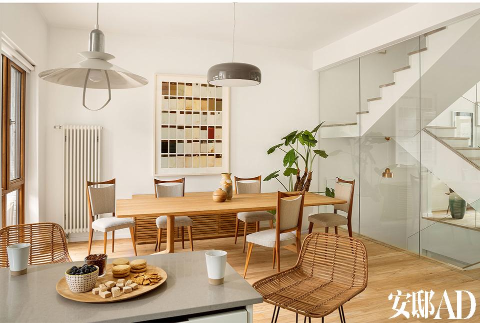楼梯间更换为玻璃墙,南北两侧的 阳光成功牵手,整个家都变得通透起来。餐厅区域,从这里可以看出,楼梯的扶手和隔墙都被换成 了更透光的玻璃材质。橡木主餐桌来自De la Espada,上方的灰色吊灯为SMithfields品牌,由Jasper Morrison设计,几把漂 亮的法式古董餐椅是20世纪中期的产品,购自一个古董集市,已经过修整和重新软包。墙上的艺术作品由Bruno'Olle创作,来自巴塞罗那一家最好的当代艺术画廊Miguel Alzueta。近处吧台旁的藤质吧凳由西班牙一家专注于定制复古产品的公司Antique Boutique设计。