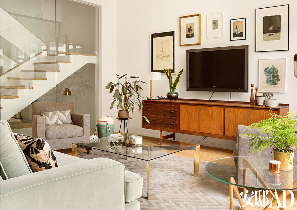 """客厅中,方形玻璃茶几由Miguel Mila设计于1950年代,购自巴塞罗那一家专门经营中古产品的家居店""""Kensington 177"""",电视柜也是那个时期的产品。墙上的艺术品大多来自网络艺术平台Little Paper Planes,最左侧的一幅由西班牙雕塑家Amadeo Gabino创作。"""