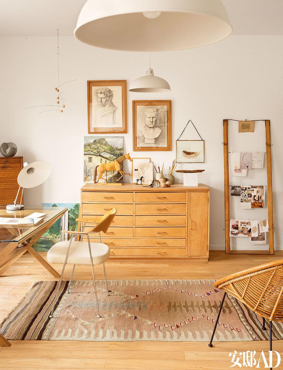 """家里的大部分家具及饰品,全部来自欧洲各地的古董市场、设计师店,或者古董拍卖会,绝对是名符其实的""""海淘""""工程。家中的画室,左侧的玻璃面写字桌为Grey品牌;桌上的白色台灯是中古产品,来自伦敦的Odyssey 20C;座椅是Robyn Day的重制品,来自Habitat。民族风的地毯来自专营复古地毯的公司Moroccan Kilim, 木质多抽屉储物柜也是来自英国的老物件,安装上了新的黄铜把手,一旁挂着很多照片的木框架来自一台老的织布机,购于古董集市。"""