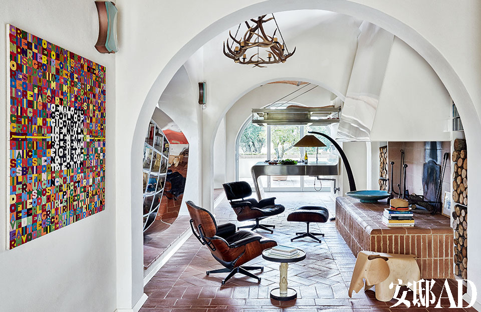 """左侧的墙壁上挂着的是Alighiero Boetti的作品。作品上方挂着的是 Pietro Chiesa为Fontana Arte设计的20世纪60年代的壁灯。接着是Ron Arad 2009年设计的书架""""Restless""""。Vintage的扶手椅和方凳是Charles &Ray Eames的设计,Vitra生产的大象凳也是。小边桌""""Corteccia"""" 是1937年Pietro Chiesa为Fontana Arte作的设计。"""
