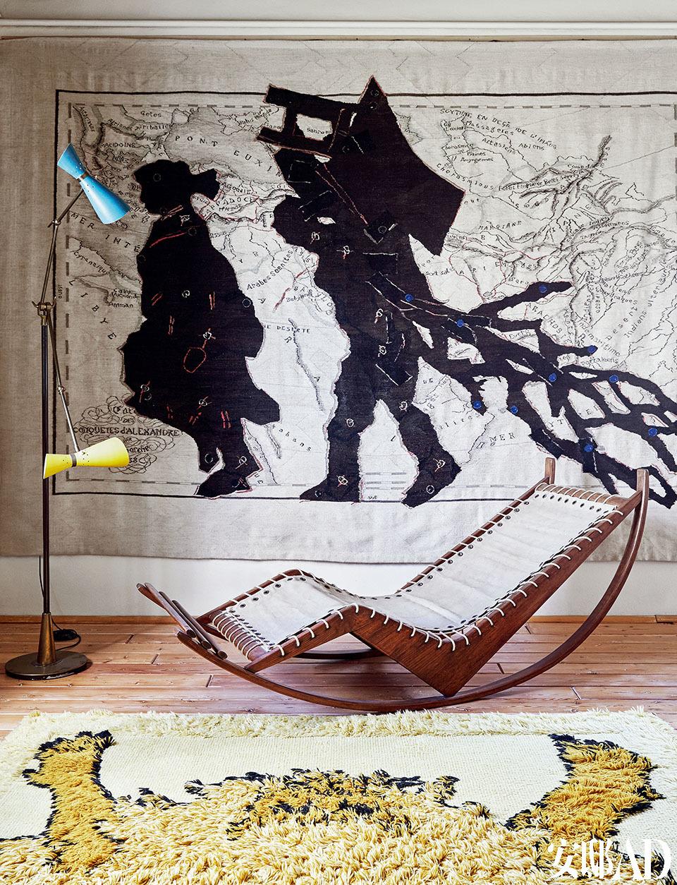 """躺椅的线条与细节,与墙 上的画作有着不谋而合的默契。在主卧房里,摇椅"""" PS16"""" 是Franco Albini 20世纪40年代的设计,用栎木结构和纯棉编织制作而成。南非艺术家William Kentridge的画作Porter Series一侧是20世纪50年代的 Stillnovo落地灯。1970年代的""""Tapizoo"""" 系列地毯是意大利建筑师Roberto Gabetti 和 Aimaro Isola的设计。"""