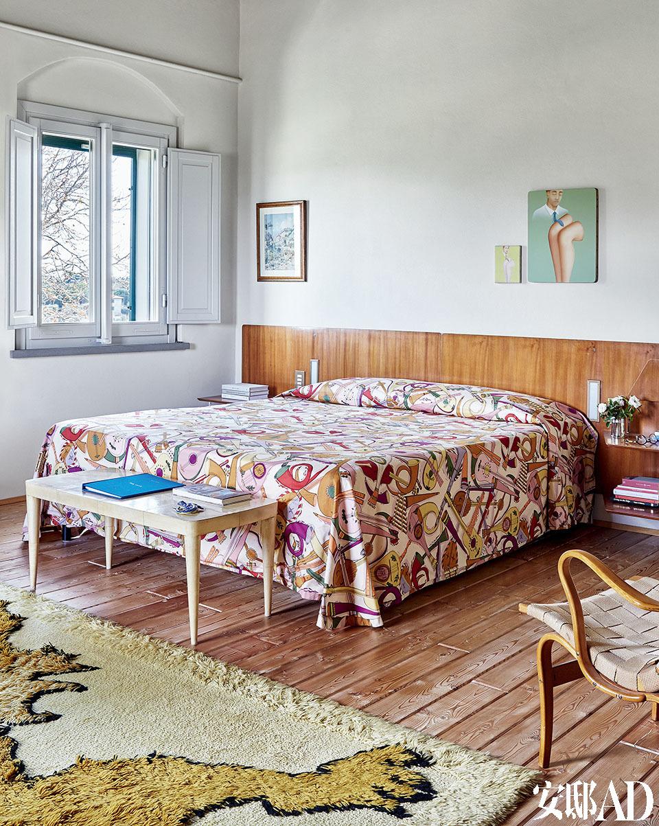 """床铺是意大利设计师Gio Pont(i 1891-1979)在1954年为Royal Naples酒店做的设计。床头上方挂着的小画是艺术家Francis Alys于1997-1998年创作的油画作品。 右侧是一张瑞典设计师Bruno Mathsson(1907-1988)设计的 20世纪50年代扶手椅""""Eva""""。"""