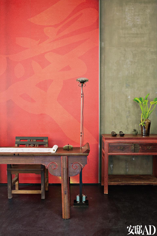 """从山洞般隐秘的入口走进,门前的小树开着红花迎接,入口的大红墙面,以书法体写着大大的""""爱""""字。其立灯为Flos经典灯款Toio(1962年的设计)搭配古董。""""这个空间展现与大自然相依的关系,相依而有,是一种生命。"""""""