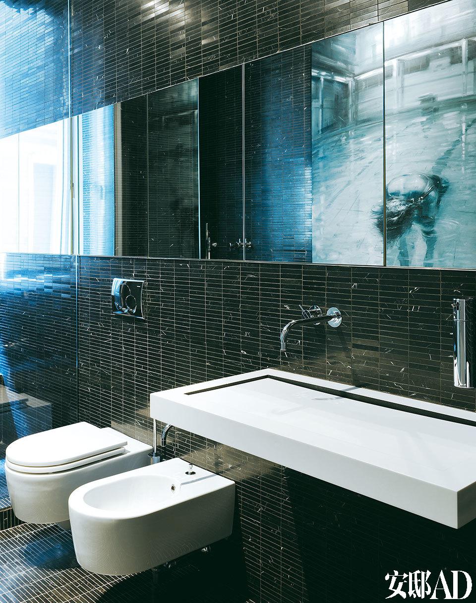 黑色的卫生间由Marquinia Marble马赛克砖(Studio Biemme 2)贴成。水龙头是Arne Jacobsen为Vola设计的产品,水池为可丽耐材质,Axolute出品。坐便器为Flamina的Link。油画的作者是Alessandro Papetti。