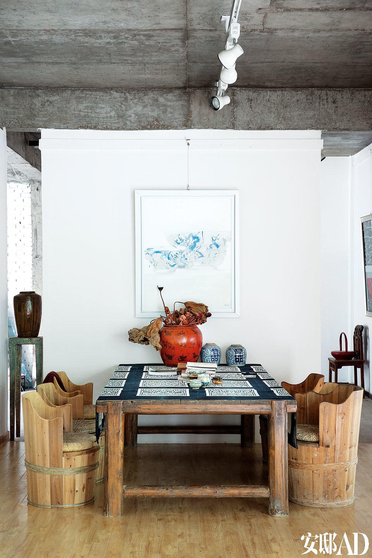 """画廊中的会议桌,桌上的古董陶胎红色大漆罐来自山西,一旁还有两只清代的青花罐子。左侧墙边立柱上的古董罐子来自汉川马口窑,6把""""火筒椅""""是对当地特有坐具的改良,冬季可在桶内放入木炭取暖。"""