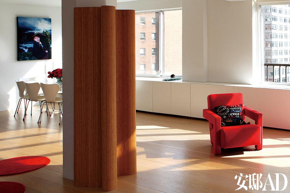 客厅与餐厅相连,其明艳的色彩与空间感,会令人暂时忘却这里是寸土寸金、车水马龙的曼哈顿。地上的红色圆形地毯购自IKEA宜家家居,红色的Felt Utrecht扶手椅是Gerrit Rietveld的设计,由Cassina出品。