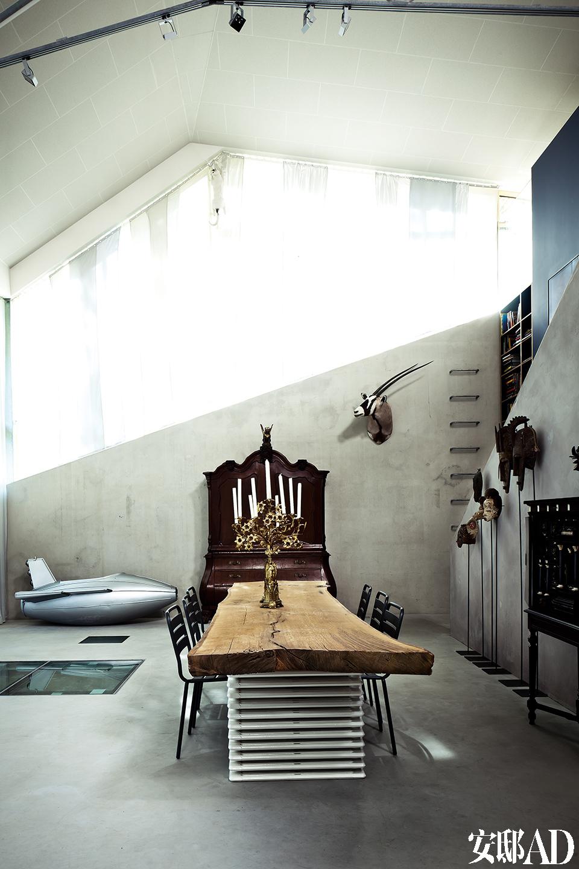浅灰色调的餐厅中,混凝土墙壁未加修饰,阳光穿越山丘和树丛,斜斜地照射进来。这个家仿佛一座巨大的容器,收纳着富有生机的室内设计元素和屋主大量的非洲艺术珍藏。
