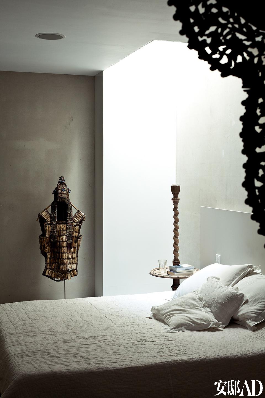 """浴室中的花瓷砖及卧室床品上细细的衍纹,在宁静优雅的气氛中,丰富了质感和层次。卧室是这个建筑中最暗的一个房间,日光透过""""灯光墙""""透射进来,看起来有点像置身于山洞中的感觉。"""