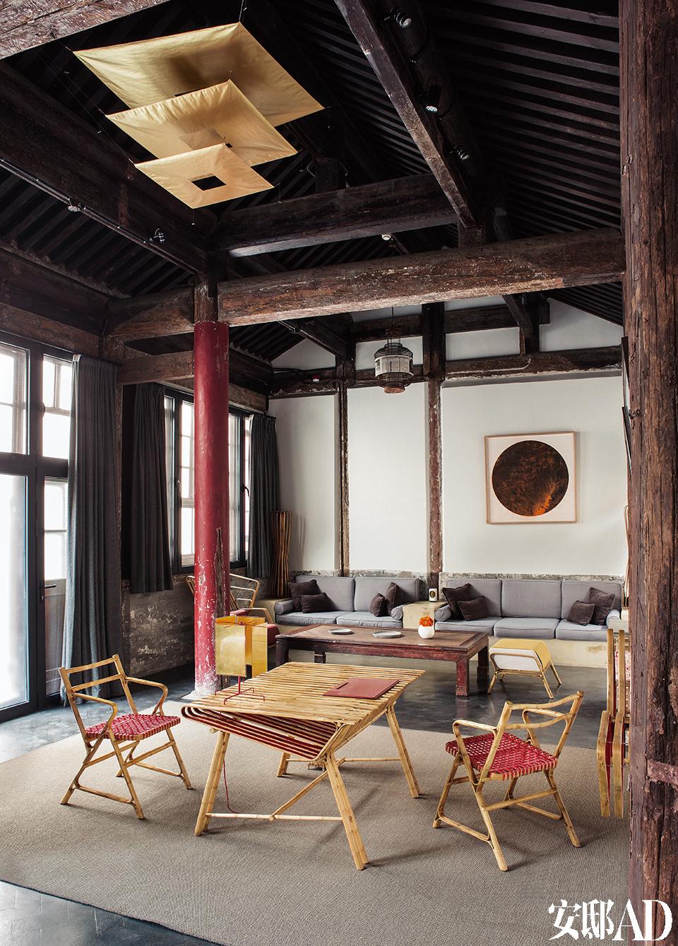"""君子不能居无竹,印度设计师 Sandeep Sangaru的系列竹编家具在古房梁下带出一种年轻的律动。最大的一间僧寮式客房""""呈祥""""有75m2,里面最大的亮点就是印度设计师Sandeep Sangaru的系列竹编家具,包括桌椅、躺椅、坐凳、书架、衣架、落地灯等多个品类,Juan在2013年的北京国际设计周""""知竹""""主题展上发现了他。远处一张红色的古董榻正面也是竹 编而成,它如今被用作了茶几。白墙上的水墨画来自画家汤国,是这间客房中的主要艺术品。金光闪闪的台灯24 Karat Blau T和吊灯Luxury Pure都来自Juan最钟爱的灯具品牌Ingo Maurer,远处的鸟笼形吊灯则是他与工匠合作,利用回收鸟笼而制作的。"""