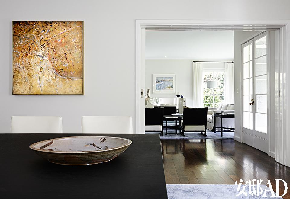 [After] 一扇推拉门可灵活决定正式客厅与餐厅的分合,墙上的油画名为《Kelly's Creek》,作者是澳大利亚画家Fred Williams,它与餐桌上的粗陶盘有着同样的粗粝质感。