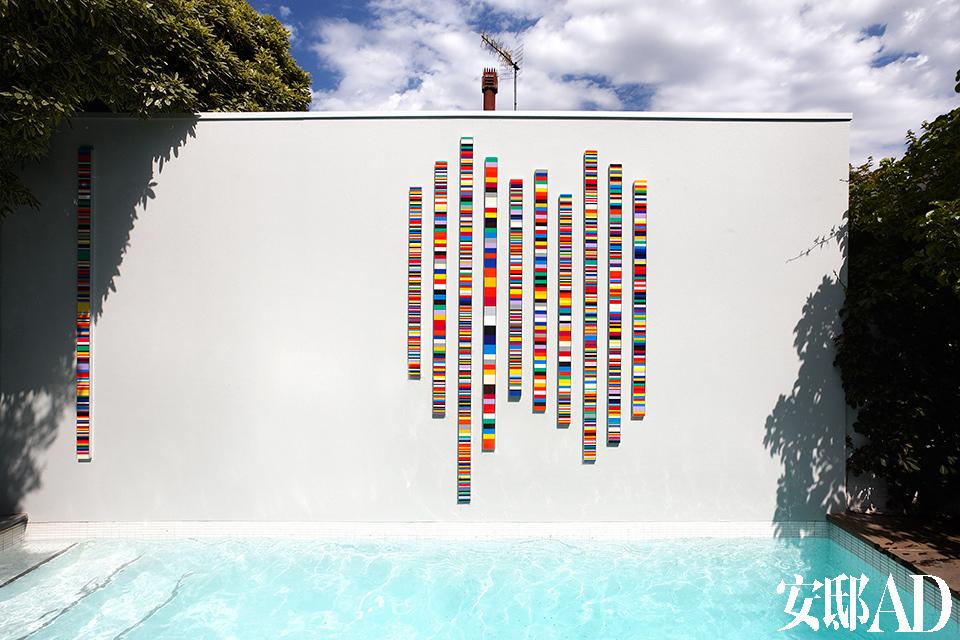 醒目的泳池背景墙上,墨尔本著名艺术家John Nicholson 创作了有机玻璃材质的壁挂式雕塑,绚丽的彩色条纹让之前院中的空阔和黯淡感一扫而空。