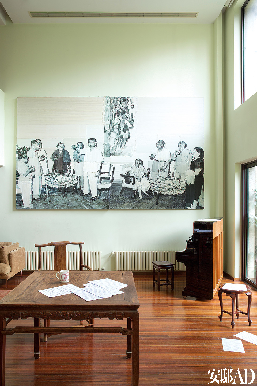"""牺牲了二层的卧室,将一层客厅改为挑高空间,""""我们不想让孩子们花太多时间在各自的卧室里,而这样的大客厅还很适合给女儿举办小型钢琴演奏会!""""客厅另一头是两层挑高的空间,孩子们在来自明末年间的黄花梨木桌上练习毛笔字,大女儿还能在这里开办小型钢琴音乐会。墙上的大幅油画来自李松松。"""