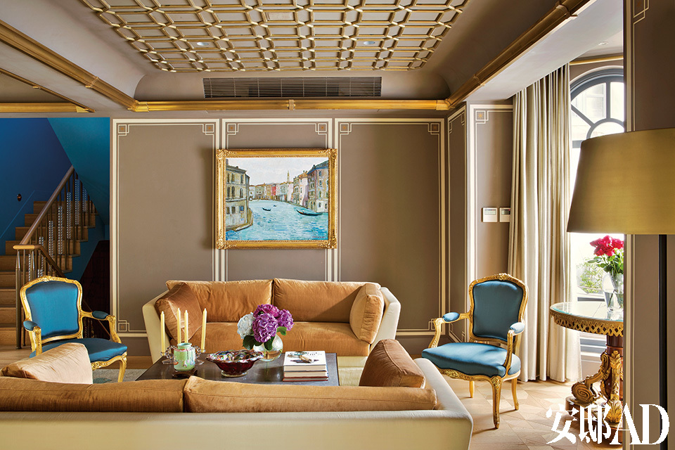 正式的起居大厅中尽是古典的装饰特征,但仍然保持着一种亲和的姿态来欢迎亲朋好友。天青蓝和灰褐色的冷色调搭配金边可谓明智之选,构建起一幕精致而稳重的家居场景。