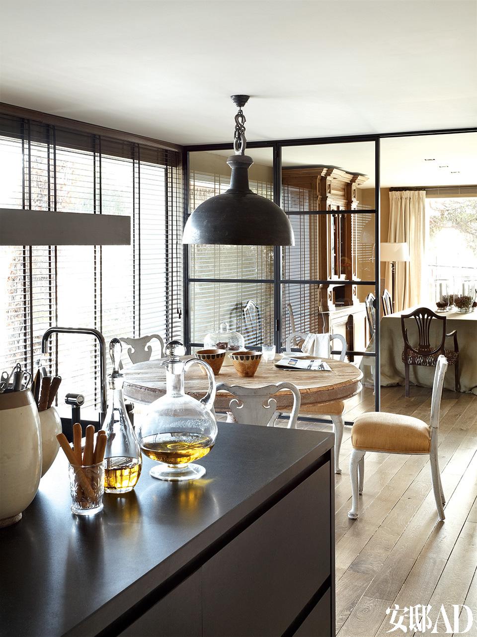 光线好是这个家的一大亮点,为了获取更多光线,厨房和餐厅之间还用了透明玻璃隔断。紧邻厨房的日常餐厅,中间摆着一张19世纪法式圆桌,Gustavian印花座椅来自瑞士。做旧的工业吊灯、铝制厨房家具、水晶油瓶等物品均可在设计师Toni的Azul Tierra商店购得。