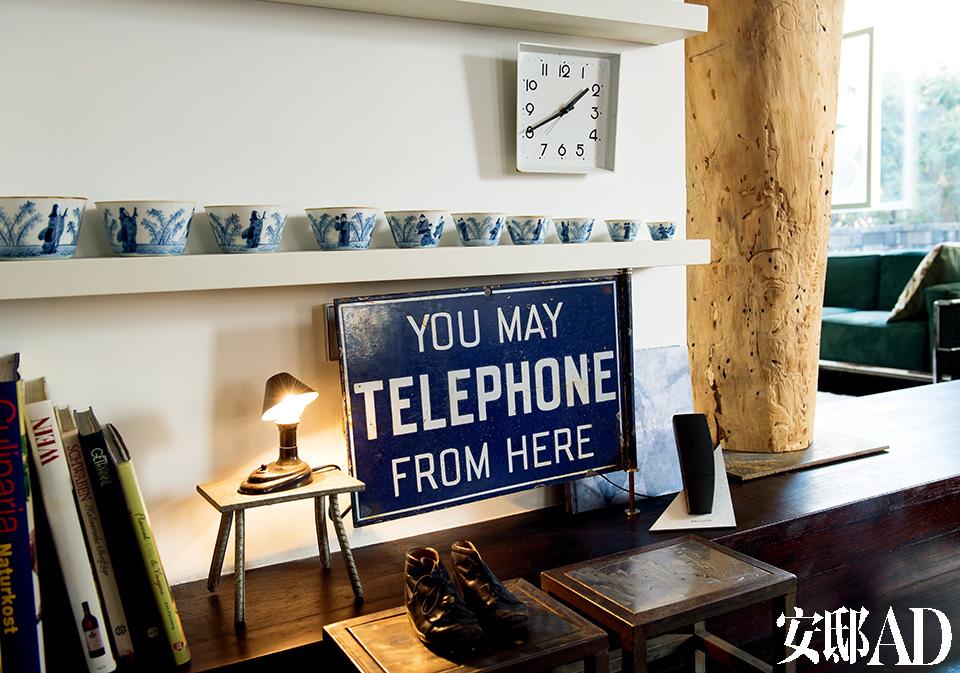 """二层休息区一角带着书香,深红色系的家具和配饰装点出一个沉静的世界。餐厅与客厅的交界处是个小小的展示区,白色搁架上的一套青花瓷器购自北京的古董市场,小的可做茶杯,大的算得上是茶碗了,它们可以精确地叠装在一起。上了漆的铁牌应该是一块国外的电话亭告示牌,Arnd从一家北京小店中找到它。发亮的Bakelit微型台灯是二战前的产品,两张金属凳子是Arnd在为他提供服务的制铁作坊中发现的,""""简洁大气的造型,各表面闪着不同的微光,我怎能让它们埋没在工厂里!"""""""