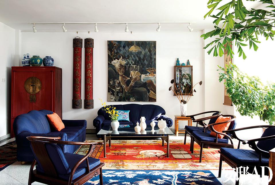 """客厅中搭配着各种浓烈的色彩。几把榆木制成的明式圈椅为现代制品,和沙发一样覆盖了岳夫人定制的软包面料。沙发是20世纪90年代初岳夫人在北京一家商店中买到的,随后对它们进行了重新设计和改造才成为今天的模样,上面的靠垫来自rochebobois罗奇堡家居。左后侧的红色木柜是清代浙江地区的产物,上面的瓷器除了左侧的一对为青花瓷仿品,其余都为明清真品。正中央的油画来自当代中国""""最有时代代表性的女画家""""夏俊娜,一旁的小壁龛中展示着岳夫人收藏的各时期中国银器。墙面上还挂着一对红底的民国时期木质对联,1991年买自北京的一家古董店。目前岳夫人已经把多年收集的老地毯都运回了汉堡,现在这个家中的地毯均来自经营商陈伟宾。 岳夫人对中国艺术和古董家具的热爱,让这个家成了一个独一无二的""""中国创造""""展示厅。"""