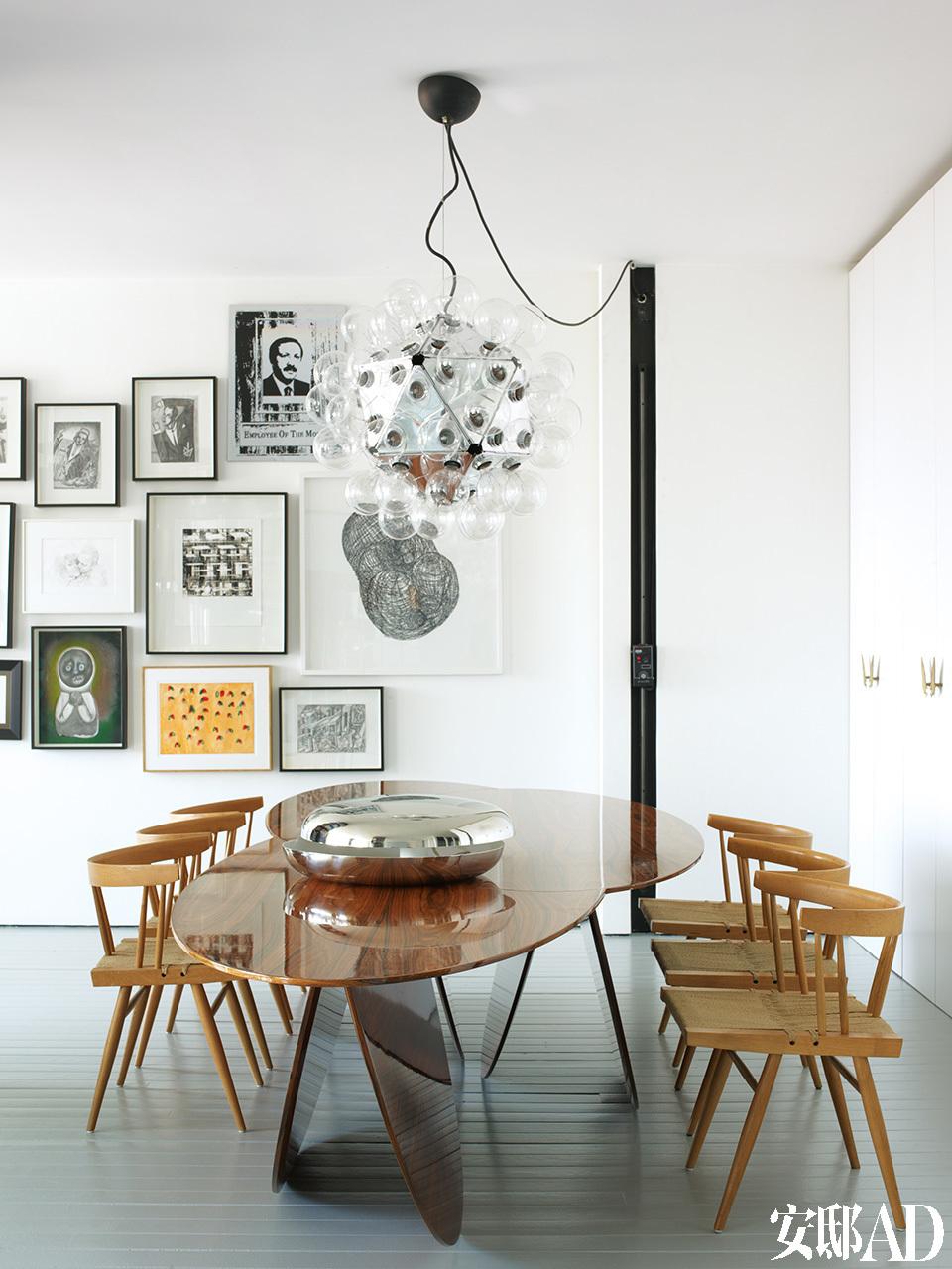 造型独特的云形餐桌,好似空间里的一件雕塑,与经典名灯、名椅搭配得相得益彰。用餐室,餐桌出自Autoban,餐椅为GeorgeNakashima,餐桌上方的天花板灯是A c h i l leCastiglioni的,橱柜把手为私人定制。