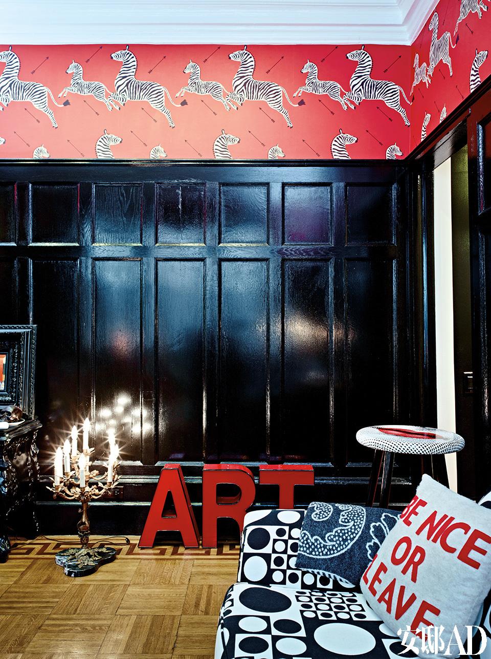 红色的ART字母组合与Piero Fornasetti的凳子都来自eBay,原来的木地板得到了保留。古典蜡烛形台灯是在路易斯安那一座伏都教建筑中发现的陈年旧物,也是从Etsy网上低价淘来的。斑马图案的红色墙纸源 自于主人最爱的电影场景,完全打破了原本黑色护墙板的沉闷。