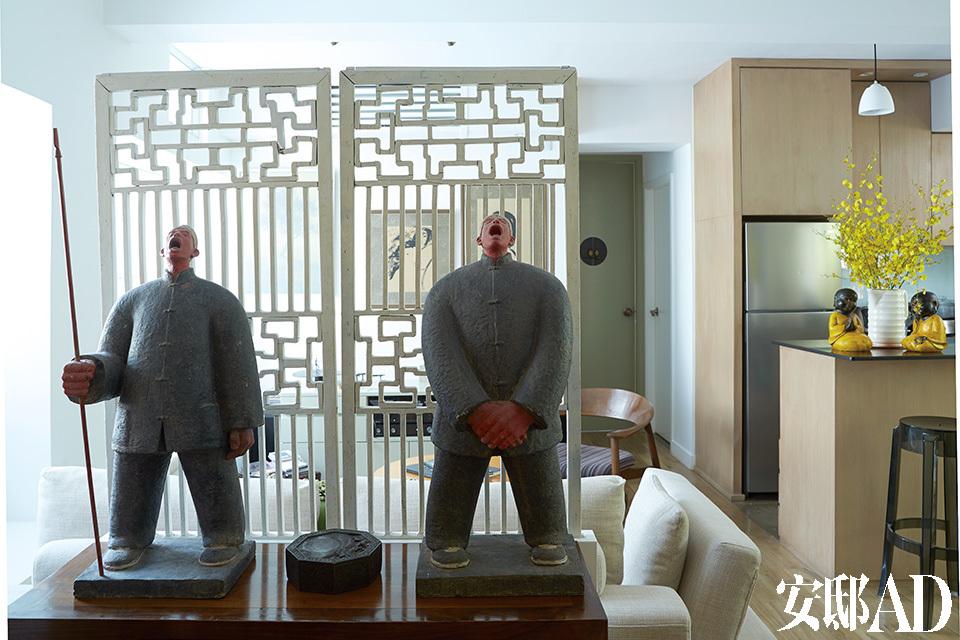 """这个家门口站岗的两尊玻璃纤维的雕塑""""农民""""像出自艺术家刘若望之手,购自香港的WellingtonGallery。雕塑后面是两扇经过刷白的古董中式门,为后方的起居室提供了私密感。"""