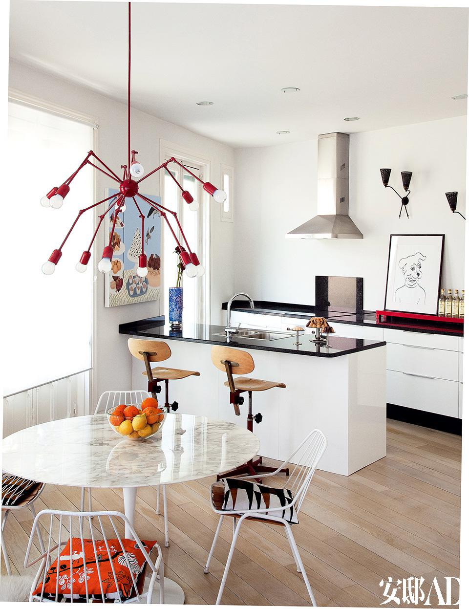 """黑白为主色调的厨房和餐厅区域,红色蜘蛛吊灯无疑是点睛之笔。厨房中,整体橱柜来自宜家家居,吸油烟机为SMEG品牌,一旁是Luis Macías的小狗素描。另一侧的墙面上挂着Rosalía Banet系列作品""""肉店之爱""""(Carnicería Love)中的肉食静物画""""Bodegón De Carne"""",购买于Espacio Mínimo画廊。墙上的法式壁灯来自La Europea。"""