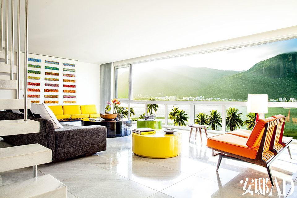 客厅硕大的落地窗面对着科尔科瓦多山的湖光山色,视野极佳。复古的黄色沙发和橘色沙发购自里约的一家古董店。客厅中央摆放着特制漆面矮桌。左面墙上挂着古巴艺术家Lauro Muller的作品。