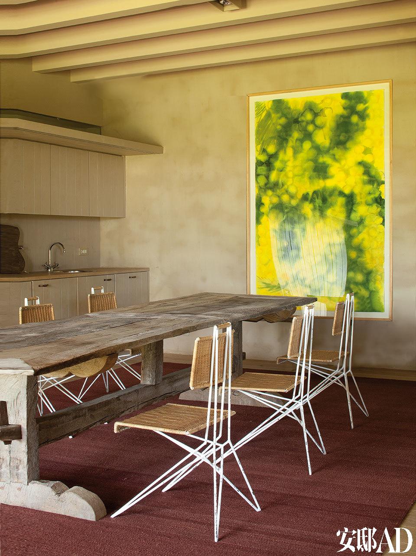 用餐区域中,质朴的木质餐桌是18世纪的乡村样式。餐椅由法国设计师Matégot设计,购自Serge Castella。墙上的含羞草水彩画来自俄罗斯艺术家Lavrenti Bruni,购于SergeCastella。厨房区域里,橱柜以及其他家具均由当地一位木匠制成,木头还被粉刷过。地面上铺着纯手工制成的茄色植物纤维 地毯。