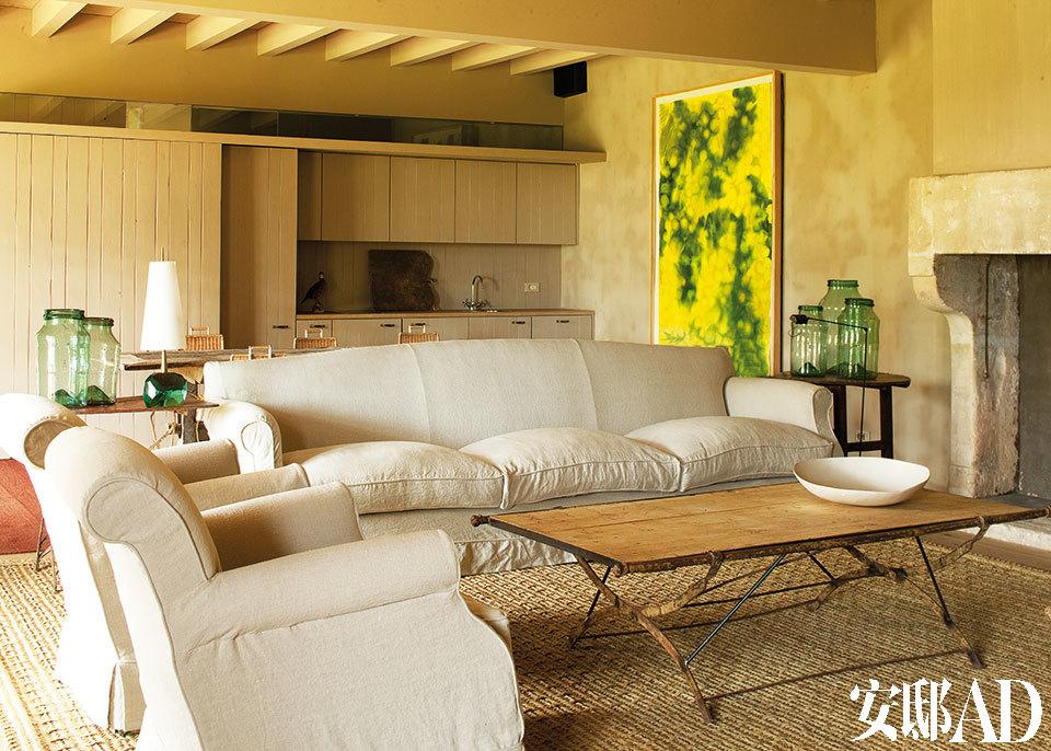 """自然色调、天然质感主导了室内的一切,让人置身于其中,不由放下心中的繁杂。餐厨区域与客厅开放相连,客厅中央的桌子本是一张营地用床,设计师Eduardo Arruga在其表面添加了一层木板,从而变成了现在的样子。桌上摆放的瓷盘来自Maria Antonia Carrión。一对扶手座椅和长沙发是设计师 Eduardo Arruga专为巴塞罗那的""""Lucca""""商店设计的产品。沙发边的红色金属小桌是20世纪初的园艺小桌,购自""""Lucca""""商店。金属小桌上摆放着 Roberto Giulio Rida设计的台灯以及两个吹制而成的加泰罗尼亚风格玻璃艺术品。这对玻璃制品是在小镇著名的集市上买到的。主人用它们来保存罐头橄榄。沙发另一旁摆放着 在""""Lucca""""商店购置的木质小桌,上面摆放着若干吹制玻璃制品。手工植物纤维地毯则出自本地一位艺术家之手。客厅里还有一个18世纪的法式石头壁炉, 特为搭配别墅而在原有基础上进行了改造。"""