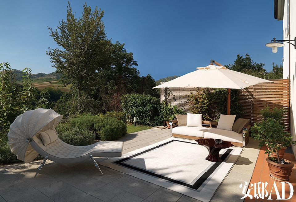 户外露台上,带棚躺椅Sveva Capitonné由Giuseppe Viganò设计,白色Galloway沙发由RobertoTapinassi和Maurizio Manzoni设计,Gorgona茶几由Alessandro La Spada设计。以上家具全部来自Visionnaire。