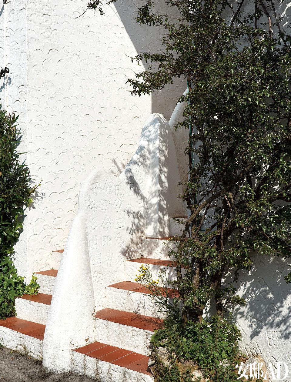 阳光与阴影的游戏、各种传统的地中海文化元素,都被设计师天真地玩味着。这个通向其中一栋房子的入口是如此天真烂漫,从分隔栏杆的形状到装饰外部选用的印花都散发着这种味道。