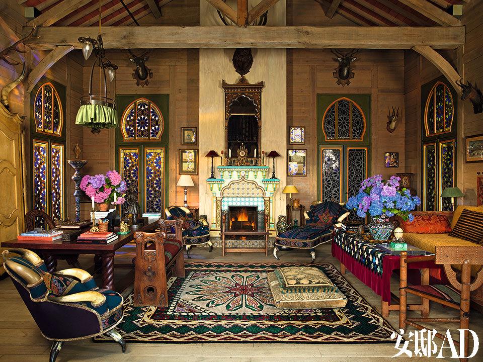 """着色玻璃门和松木镶板并排围绕着多功能的客厅,这间屋子占据了这幢俄罗斯风格建筑的大部分面积。整座住宅建于上世纪80年代,是Pierre和他的已故伴侣、时装设计大师Yves Saint Laurent的度假别院。东方风格的壁炉架和镜子为19世纪法国制造,奥地利牛角椅和躺椅都覆上了基里姆毯子;地板是19世纪俄罗斯制造的,左侧的大桌和一旁经雕刻的长凳亦是。充满童话意味的俄罗斯装饰风格充盈一室,其色彩与光泽都让人不禁想起YSL在1976年推出的"""" 俄罗斯芭蕾舞团""""系列里那些丝绒与绸缎。"""