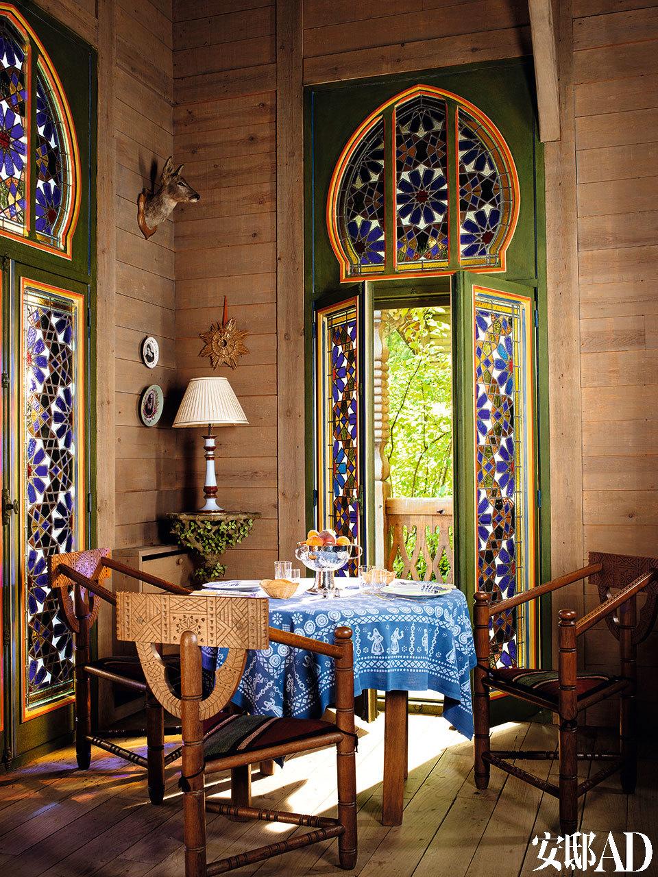 客厅一角是用餐区,俄式花园的木质座椅是大约在1900年前后,于Talashkino的作坊生产的。古董级的着色玻璃反射出黄、绿、蓝、红等迷离的光线,令人怀念起YSL在上世纪80年代创造的那些色彩鲜明的套装。