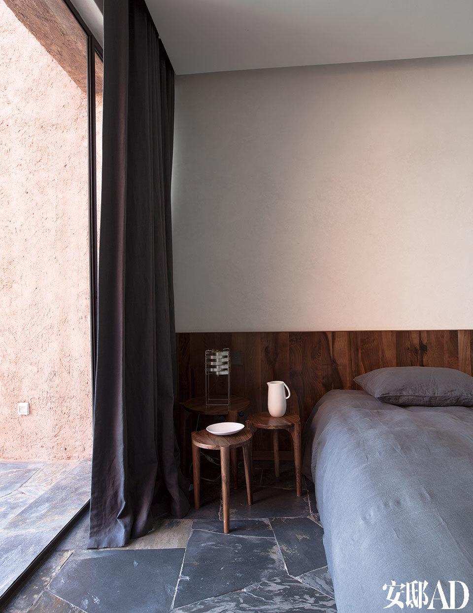 一间卧室中,床头的一组胡桃木小桌同样是来自Ko的设计,茶几上的陶器是设计师Nelson Sepulveda的作品,炭色棉质窗帘来自Dominique Kieffer。当地工匠那细细琢磨的手工艺,为整个家附上了一种生命的温润。