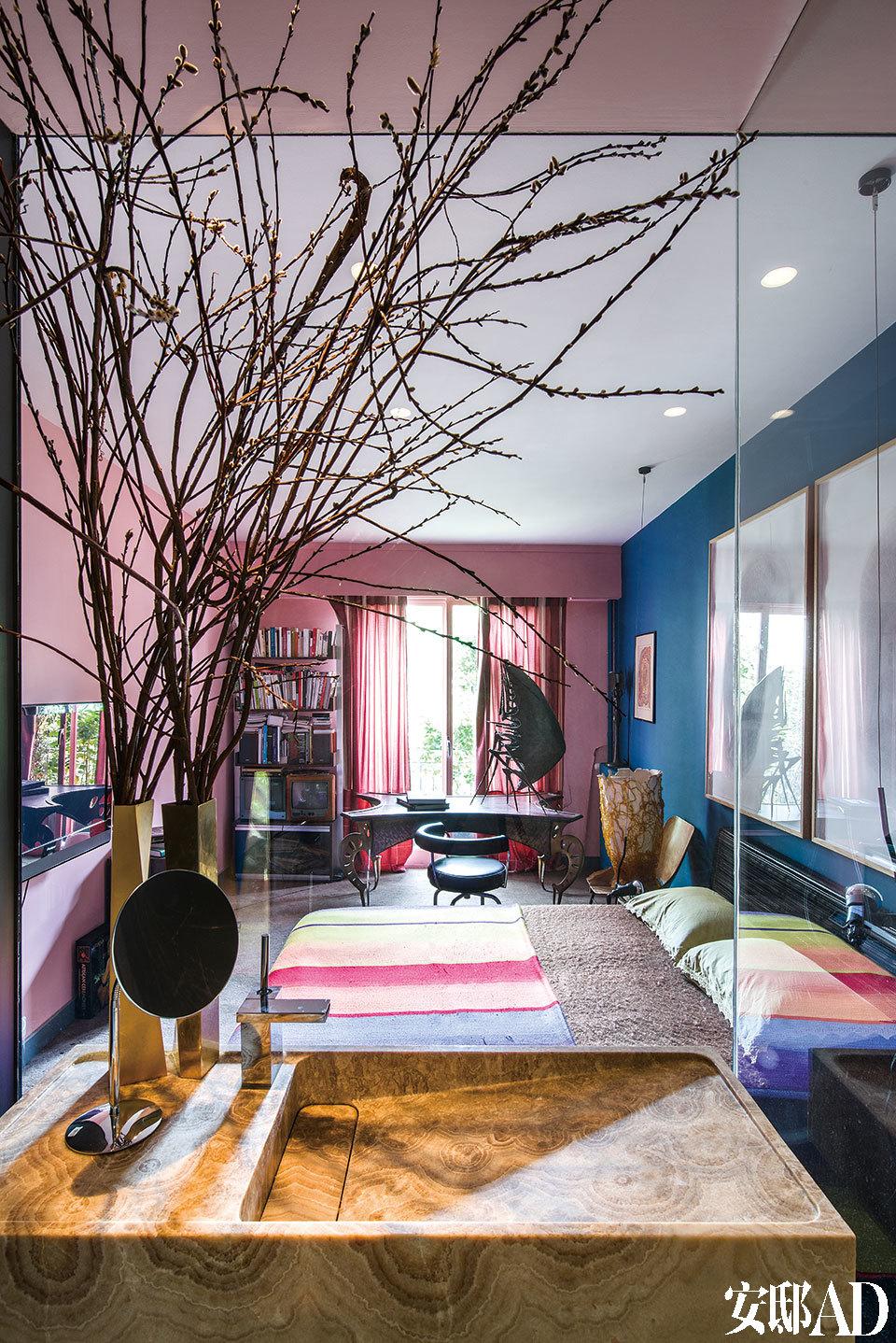 """浴室与卧室仅相隔一面透明玻璃,其余墙面进行了土耳其缟玛瑙搭配混凝土特殊处理而成;桌边的黑色转椅""""LC7""""材质为皮革和不锈钢,Le Corbusier出品。"""