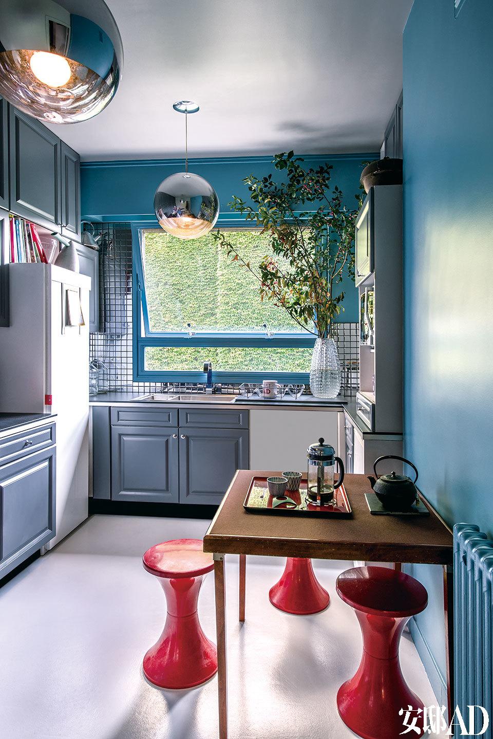 """厨房内圆形银色镜面吊灯来自Tom Dixon;红凳子""""Tam Tam"""",由Henri Massonet设计。"""