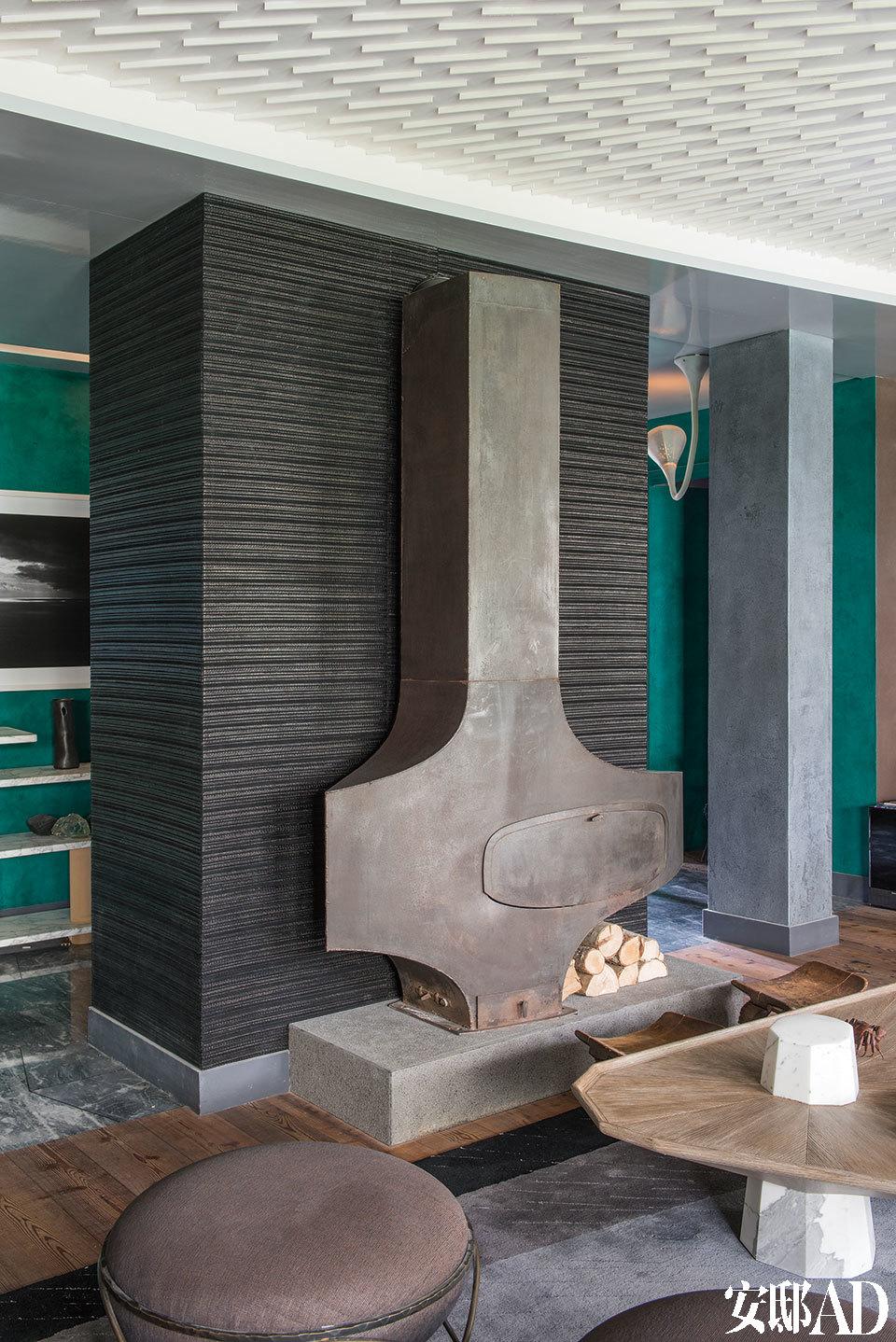 将起居室与门厅隔开的是一面柱子般的小墙,包裹表面的黑色织物面料采用皮革、羊毛和Lurex织物制成,由来自比利时布鲁塞尔的Charles Schambourg创作。